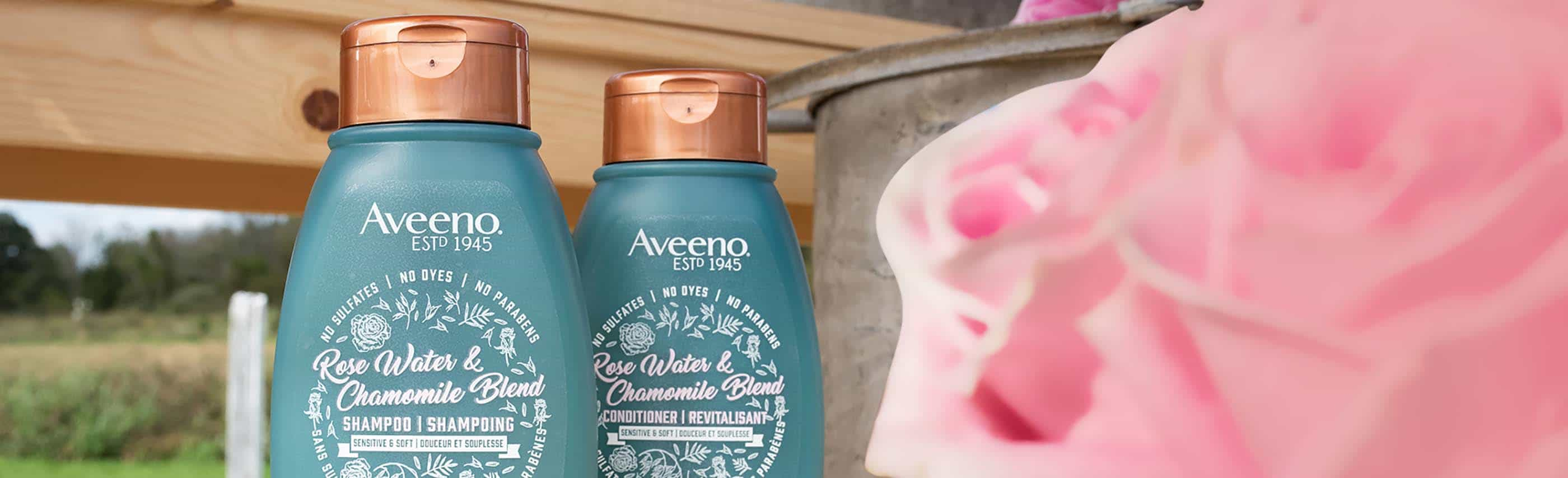 two aveeno rose water and chamomile product bottles behind a rose
