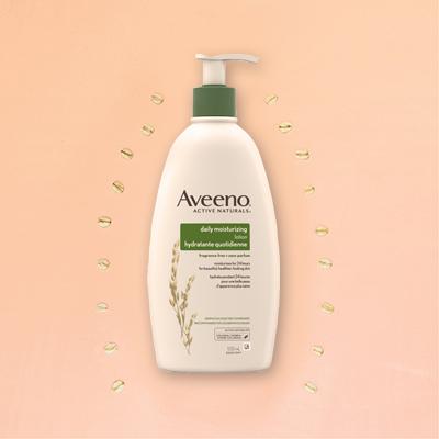 aveeno moisturizing lotion pump on peach background flatlay