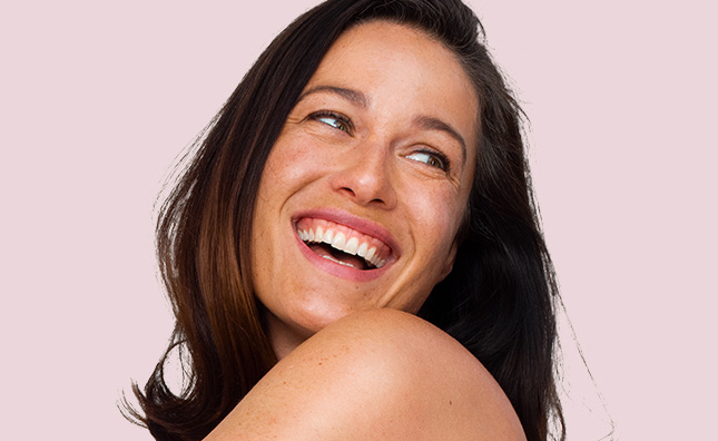 brunette woman smiling against a light pink background