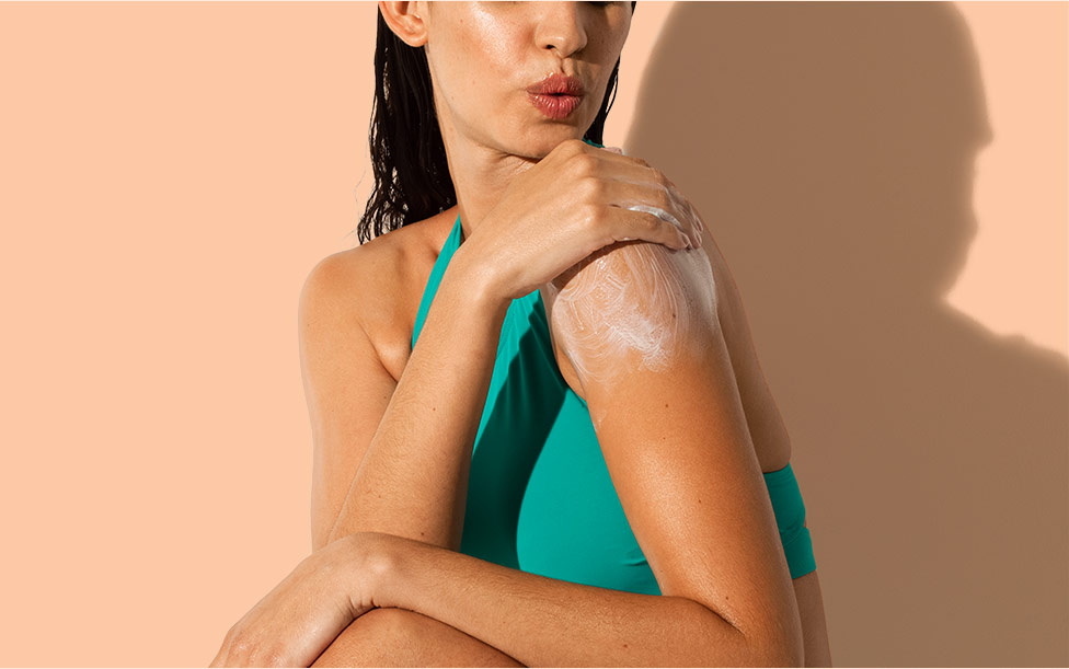 close up of woman putting aveeno sunscreen on her shoulder