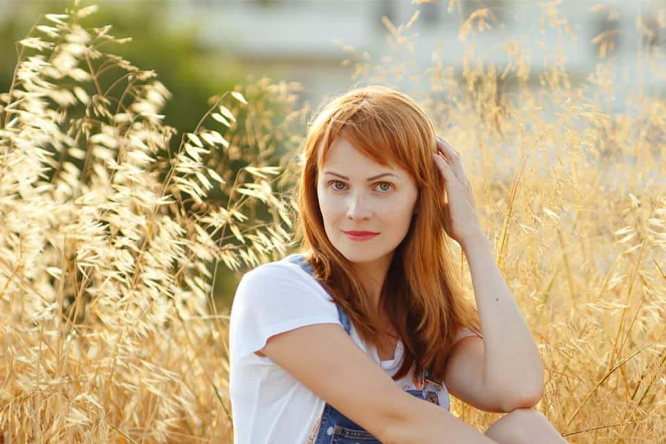 red hair woman in white shirt with hand againt her hair