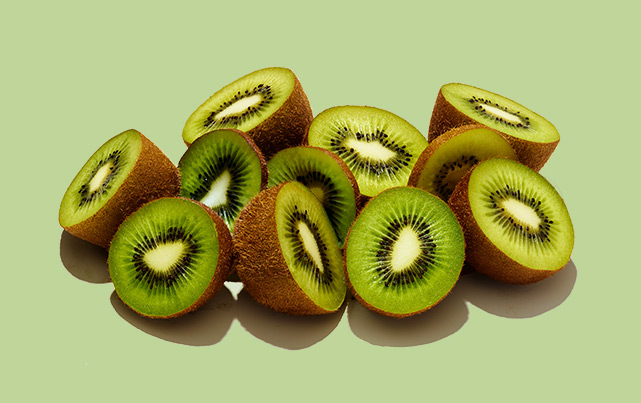 half kiwi fruit against a green background