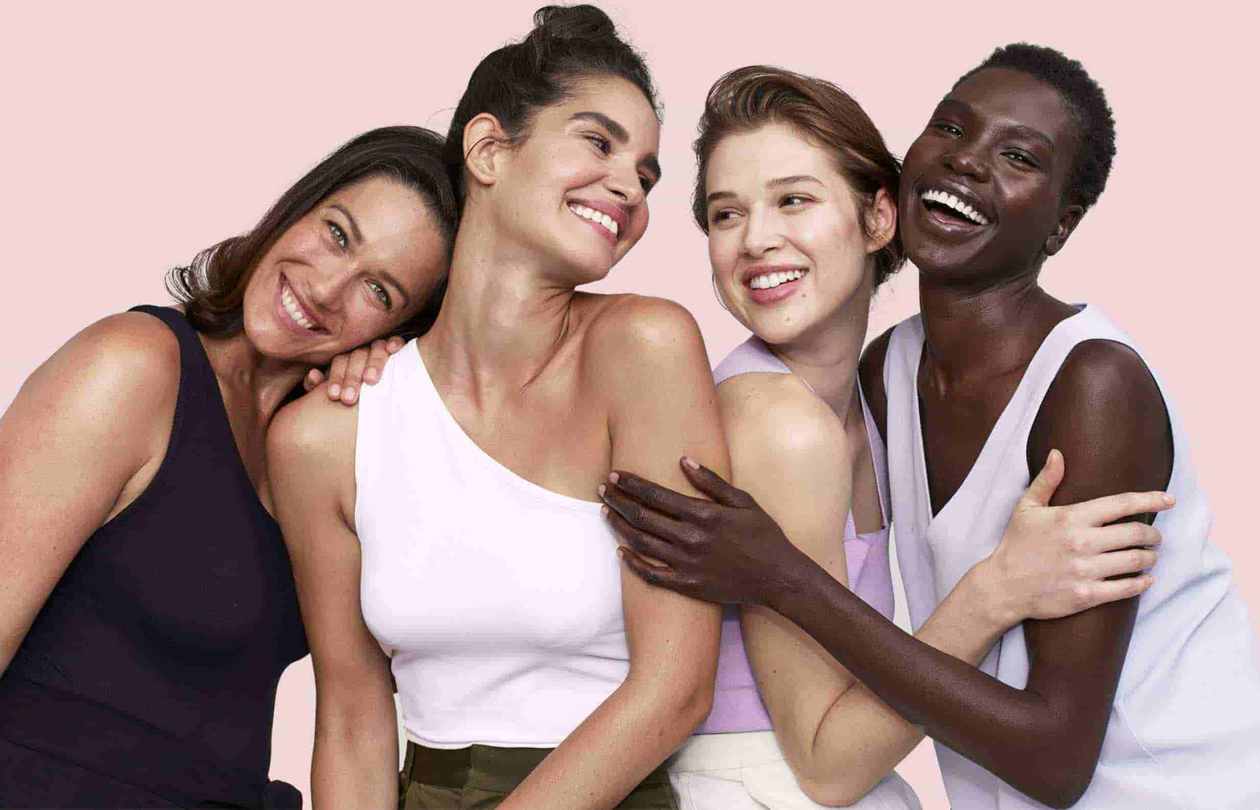 four women smiling and hugging together